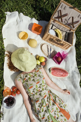 Young woman lying on picnic blanket, overhead view