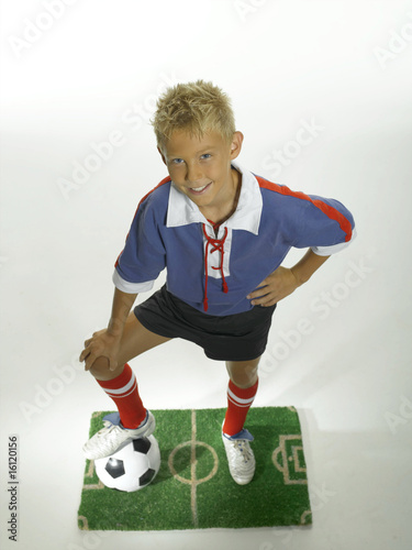 Boy (8-11) with foot on football, hand on hips
