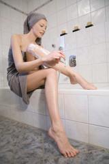 Junge Frau rasiert ihre Beine