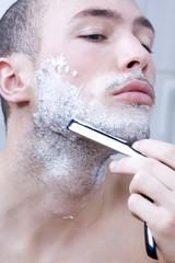 Mann rasiert sich mit Rasiermesser