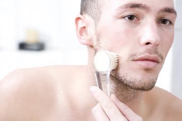 Mann massiert Gesicht mit Pinsel