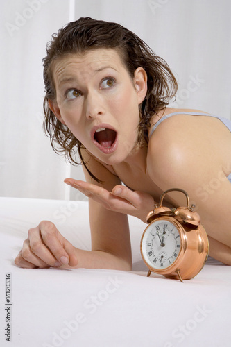 Young woman lying on bed with alarm clock