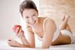 Junge Frau hält einen Apfel, lächelnd