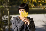 Germany, Bavaria, Portrait of a young woman holding a leaf, smiling
