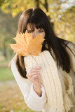 Brunette woman hiding behind autumn leaf, portrait
