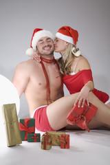 Sexy Weihnachten, Junges Paar mit Santa Claus Outfits und Geschenken