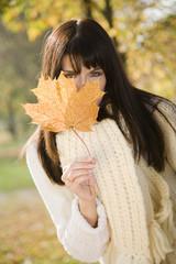 Brunette junge Frau hinter Herbstblatt