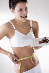 Junge Frau überprüft ihre Taille mit Maßband, mit Schokolade daneben, Versuchung