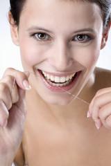 Junge Frau benutzt Zahnseide für ihre Zähne