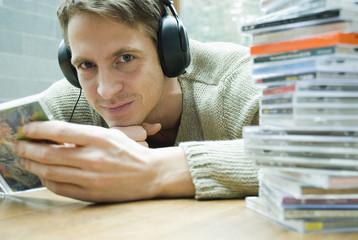 Mann mit Kopfhörern halten CD-Cover in den Händen