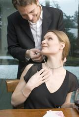 Mann Kette anlegen Hals der Frau