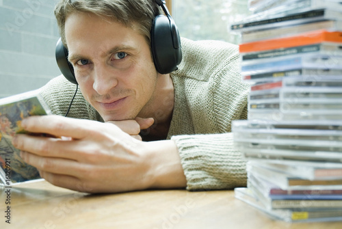 Man with headphones holding CD cover in hands