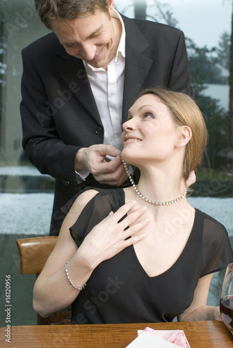 Man fastening necklace on woman's neck