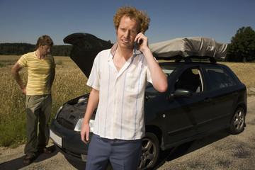 Deutschland, Bayern, Zwei Freunde mit kaputten Auto