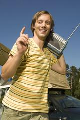 Deutschland, Bayern, Junger Mann tragen einen Transistor-Radio auf der Schulter