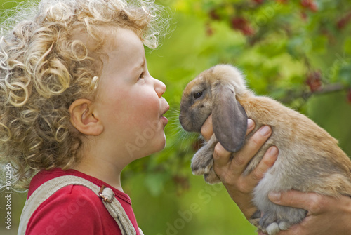 Blonde girl (4-5) with curly hair holding rabbit, portrait
