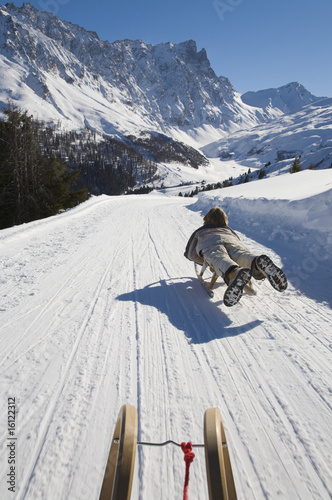 Switzerland, Graubuenden, Savognin, Boy (8-9) sledging, rear view