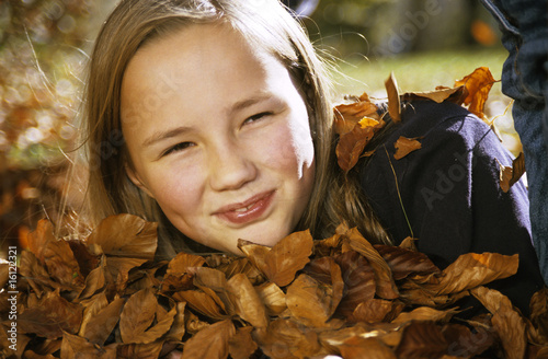 Girl (10-11) with autumn leaves, portrait