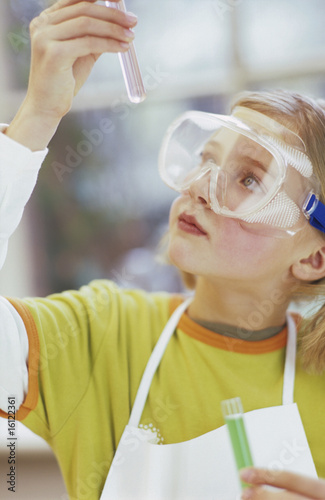 Girl (8-9) wearing protective goggles with test tube