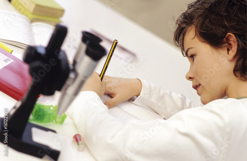 Boy (8-9) sitting by microscope, writing