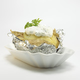 Baked potato with curd cheese in foil, close-up