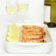 Prawns with lemon slices on crushed ice and white wine, close-up