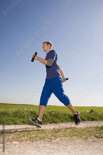 Young man jogging, carrying dumbbells