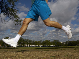 Man's legs running outdoors in a park