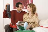 Paar sitzen auf dem Sofa, halten Toaster und Socken