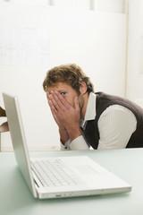 Junger Mann sitzen mit Laptop, Gesicht mit den Händen bedeckt