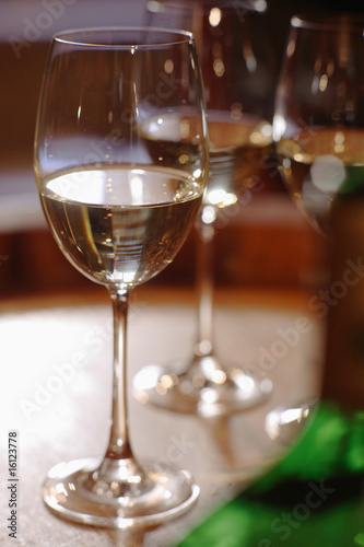 White wine bottle and glasses on wine cask, close-up