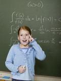 Girl (6-7) standing by blackboard, solving arithmetic problem