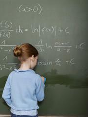 Mädchen stehen vor der Tafel, die Lösung Rechenaufgabe