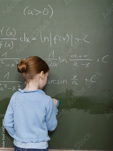 Girl standing in front of blackboard, solving arithmetic problem