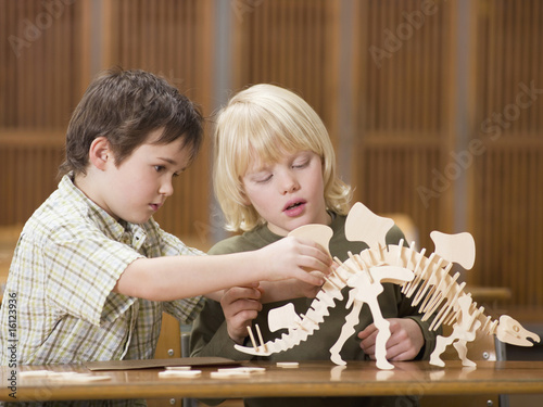 Boys (4-7) sitting with dinosaur skeleton, close-up