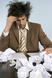 Businessman sitting at desk with crushed papers, close-up