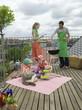 Paar mit Kindern auf dem Balkon, mit Grill