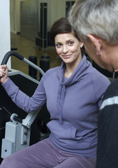 Woman in gym using exercise machine with senior man watching