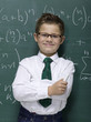Boy (10-11) leaning against blackboard, smiling, portrait, close-up