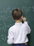 Boy (10-11) writing on blackboard, rear view