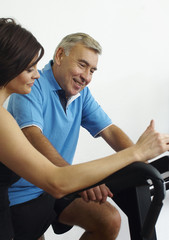 Woman and man in gym on exercise machines