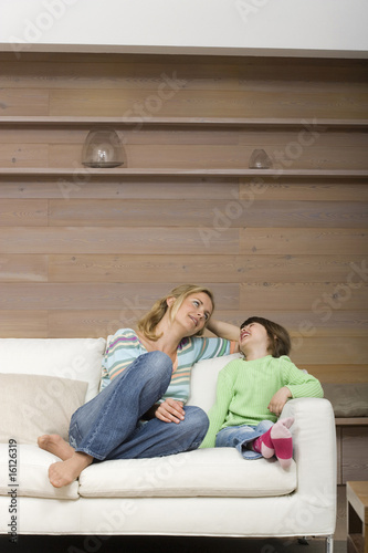 Mother and daughter (6-7) sitting on sofa, portrait