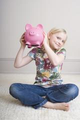 Mädchen halten Sparschwein, Portrait