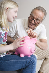 Enkelin und Großvater Opa, Enkelin halten Sparschwein, lächeln, Porträt