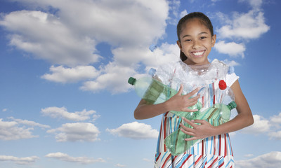 Young girl outdoors holding empty plastic bottles