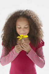 Young girl smelling flower indoors
