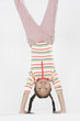 Young girl doing handstand indoors
