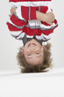 Young boy indoors hanging upside down