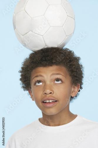 Young boy indoors balancing soccer ball on his head