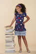 Young girl standing by a stack of books indoors